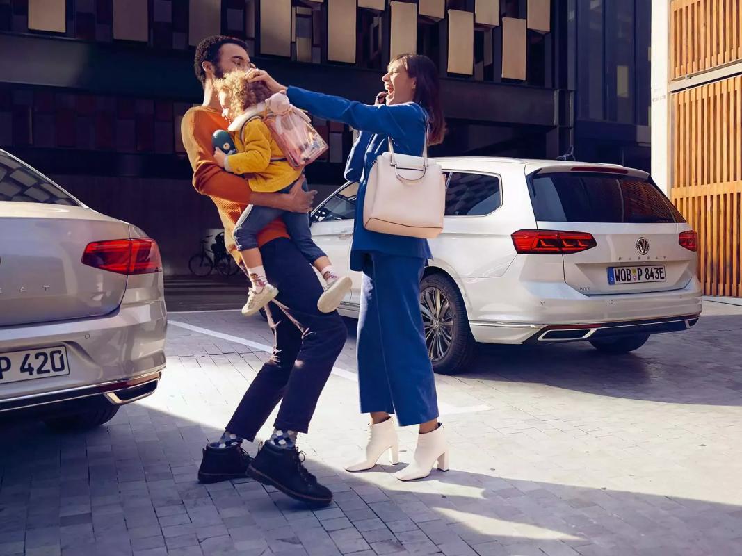 Couple avec un enfant à côté de la nouvelle Passat GTE Volkswagen